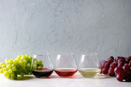 Variety of wine. Red, rose and white wine in old fashion glasses with bunches of grapes on white marble table. Copy space