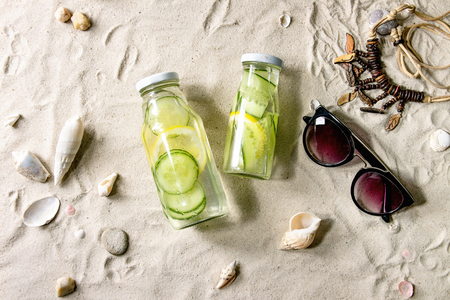 Summer theme. Two glass bottles with lemon and cucumber infusion sassy water, shells, sea stones, sunglasses, wooden beads, on white sand as background. Flat lay