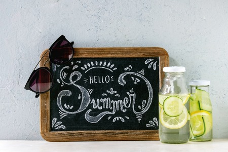 Summer theme. Chalk lettering Hello summer on vintage chalkboard, sunglasses and two glass bottles with sassy lemon and cucumber water on white marble table with concrete wall at background. Foto de archivo - 122795915