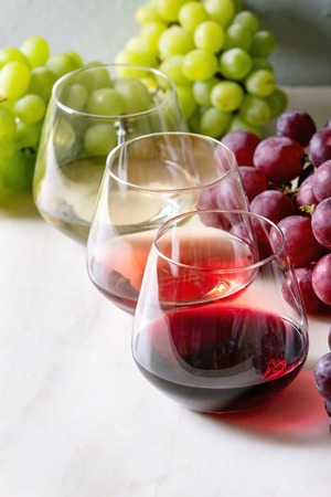 Variety of wine. Red, rose and white wine in old fashion glasses with bunches of grapes on white marble table