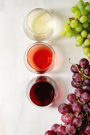 Variety of wine. Red, rose and white wine in old fashion glasses with bunches of grapes. White marble background. Flat lay, space Banco de Imagens