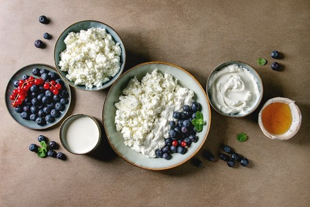 Dairy produce for breakfast. Cottage cheese, plain yogurt, milk, cream, honey, blueberries and red currant berry in ceramic bowl over brown texture background. Healthy eating. Flat lay, space