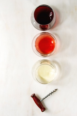 Variety of wine. Red, rose and white wine in old fashion glasses with vintage corkscrew. White marble background. Flat lay, space 스톡 콘텐츠