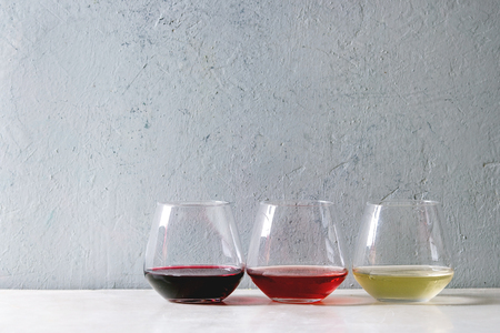 Variety of wine. Red, rose and white wine in old fashion glasses in row on white marble table. Copy space Imagens