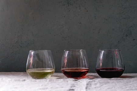 Variety of wine. Red, rose and white wine in old fashion glasses in row on grey linen table cloth. Copy space