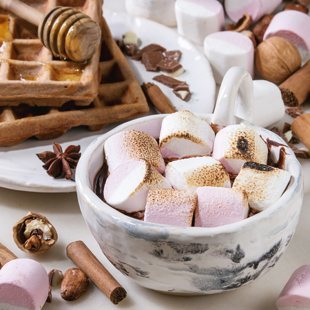Ceramic cup of hot chocolate with marshmallow s'mores with homemade honey wafers and ingredients above over white marble table. Winter drink. Close up. Square image Stok Fotoğraf - 122795951