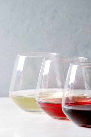 Variety of wine. Red, rose and white wine in old fashion glasses in row on white marble table. Copy space 스톡 콘텐츠