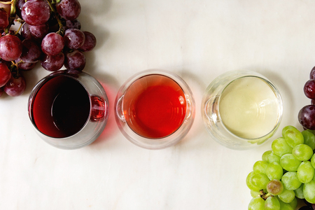 Variety of wine. Red, rose and white wine in old fashion glasses with bunches of grapes. White marble background. Flat lay, space 스톡 콘텐츠