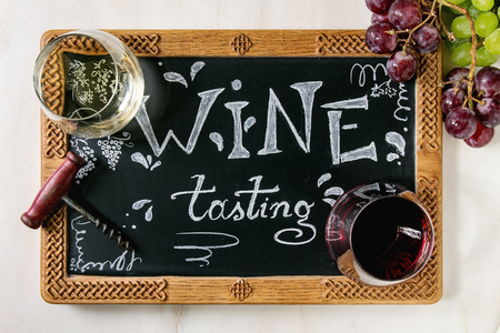 Variety of wine. Red and white wine in old fashion glasses, corkscrew, bunches of grapes, decorative chalkboard with handwritten chalk lettering Wine tasting. White marble background. Flat lay, space
