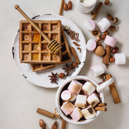 Ceramic cup of hot chocolate with marshmallow s'mores with homemade honey wafers and ingredients above over white marble table. Winter drink. Flat lay, space. Square image Stok Fotoğraf - 122795969