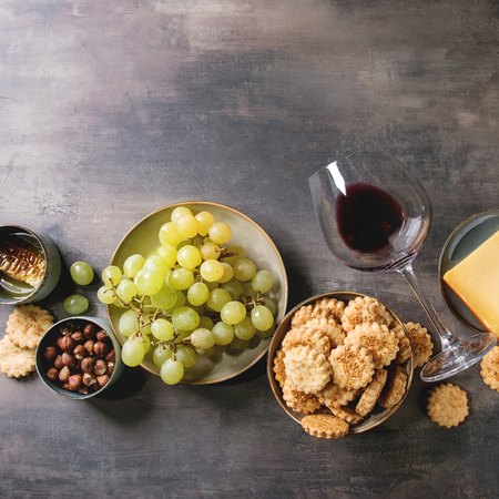 Wine snack. Cheese, grapes, nuts, cheese crackers cookies, honeycombs with laying glass of red wine and knife over dark texture background. Flat lay, space. Square image
