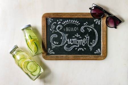 Summer theme. Handwritten chalk lettering Hello summer on vintage chalkboard, sunglasses and two glass bottles with sassy lemon and cucumber water over white marble background. Flat lay, space Foto de archivo - 122795979
