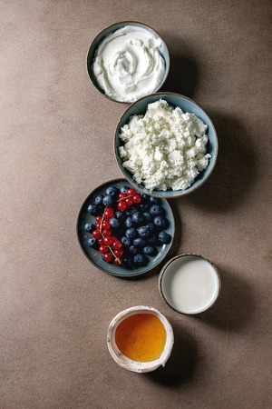 Dairy produce for breakfast. Cottage cheese, plain yogurt, milk, cream, honey, blueberries and red currant berry in ceramic bowl in row over brown texture background. Flat lay, space