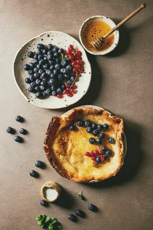 Fresh baked Dutch baby pancake in ceramic plate served with blackberry and red currant berries, bowl of honey, jug of cream, vintage sieve over beige background. Flat lay, space
