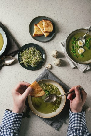Man starting dinner. Variety of green vegetable soup asparagus, broccoli or pea, decorated by greens, cream, oil, in ceramic bowls. Mans hands with spoon. Grey spotted background. Flat lay, space
