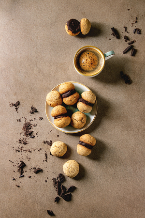 Baci di dama homemade italian hazelnut biscuits cookies with chocolate cream served in ceramic plate with cup of espresso coffee over brown texture background. Flat lay, space