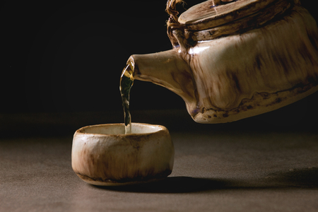 Pouring from handmade craft teapot hot green tea in traditional chinese clay ceramic cup standing on dark table with black background. Copy space