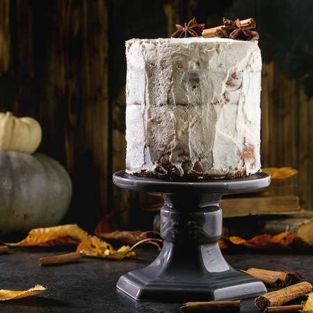 Autumn homemade white naked cake decorated by cinnamon sticks and anise on cake stand with yellow leaves and decorative pumpkins above on black table. Dark rustic style. Square image