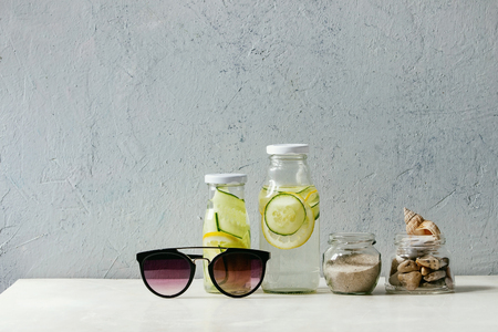 Summer theme. Two glass bottles with lemon and cucumber infusion sassy water, seashells and sand in glass jars, sunglasses on white marble table, concrete wall at background.