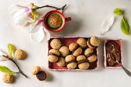Baci di dama homemade italian hazelnut biscuits cookies with chocolate cream served in ceramic plate with red cup of espresso coffee and magnolia flowers over white marble background. Flat lay, space