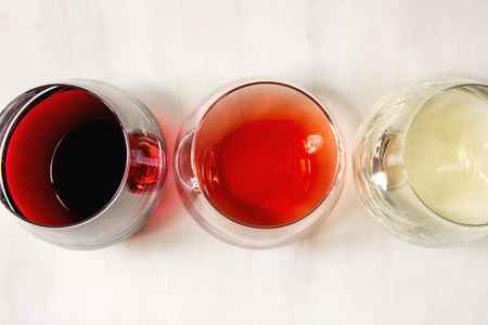 Variety of wine. Red, rose and white wine in old fashion glasses. White marble background. Flat lay, space