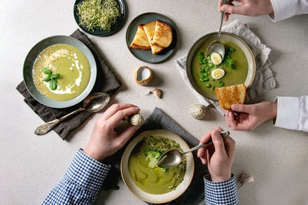 Family dinner. Variety of green vegetable soup asparagus, broccoli or pea, decorated by greens, cream, oil, in ceramic bowls. Mans hands with spoon. Grey spotted background. Flat lay, space
