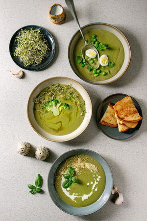Variety of green vegetable soup asparagus, broccoli and pea, decorated by greens, vegetables, quail eggs, cream, olive oil, in ceramic bowls over grey spotted background. Flat lay, space
