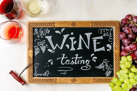 Variety of wine. Red, rose and white wine in old fashion glasses, corkscrew, bunches of grapes, chalkboard with handwritten chalk lettering Wine tasting. White marble background. Flat lay