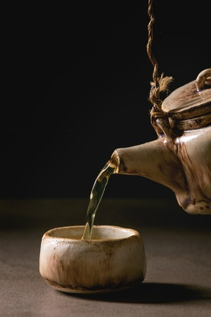 Pouring from handmade craft teapot hot green tea in traditional chinese clay ceramic cup standing on dark table with black background. Copy space Banque d'images