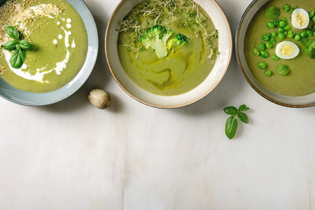 Variety of green vegetable soup asparagus, broccoli and pea, decorated by greens, vegetables, quail eggs, cream, olive oil, in ceramic bowls in row over white marble background. Flat lay, space Stock Photo