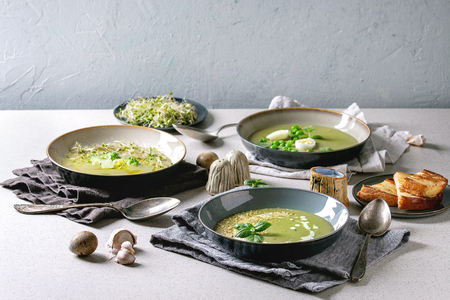 Variety of green vegetable soup asparagus, broccoli and pea, decorated by greens, vegetables, quail eggs, cream, olive oil, in ceramic bowls over grey spotted table with ingredients above.