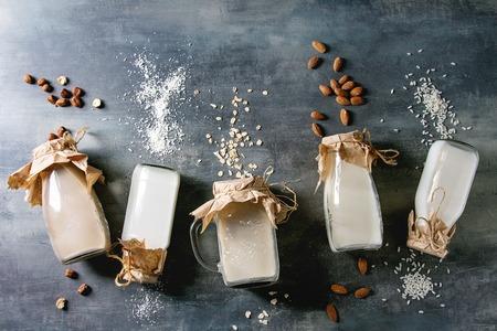 Varietà di noci senza lattosio vegane non lattiero-casearie e latte di grano mandorle, nocciole, cocco, riso, avena in bottiglie di vetro in fila con ingredienti sopra su sfondo blu trama. Disposizione piatta, spazio Archivio Fotografico