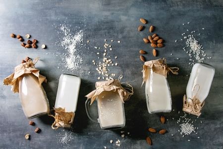 Variety of non-dairy vegan lactose free nuts and grain milk almond, hazelnut, coconut, rice, oat in glass bottles in row with ingredients above over blue texture background. Flat lay, space Reklamní fotografie