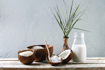 Variety of coconut products milk in glass bottle, oil and flakes in shell, fresh broken coconut on old wooden table with grey wall at background. Healthy eating, copy space 写真素材