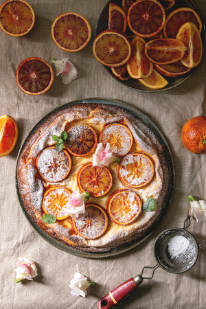 Homemade Cheesecake with sicilian blood oranges, decorated by edible flowers, mint leaves and sugar powder served in plate with cutted oranges above over grey linen table cloth. Flat lay, space Stock Photo