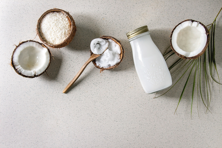 Variety of coconut products milk in glass bottle, oil and flakes in shell, fresh broken coconut on grey spotted background. Healthy eating. Flat lay, copy space