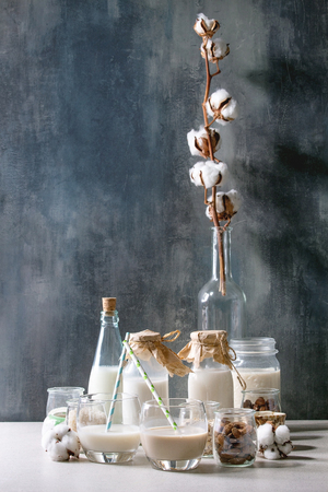 Variety of non-dairy vegan lactose free nuts and grain milk almond, hazelnut, coconut, rice, oat in glass bottles with cotton flowers on white table with blue background. Imagens