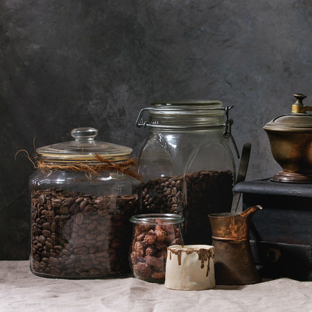 Coffee collection. Roasted black coffee beans in jar, vintage coffee grinder, jezve pot, cream jug, sweet sugared almond standing on table with linen table cloth. Square image Stock Photo