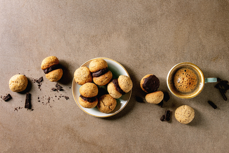 Baci di dama homemade italian hazelnut biscuits cookies with chocolate cream served in ceramic plate with cup of espresso coffee over brown texture background. Flat lay, space Stock Photo