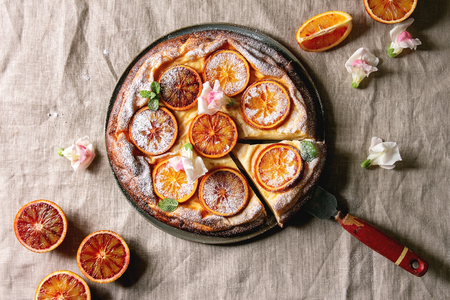 Cutted Homemade Cheesecake with sicilian blood oranges, decorated by edible flowers, mint leaves, sugar powder served in plate with cutted oranges above over grey linen table cloth. Flat lay, space Stock Photo