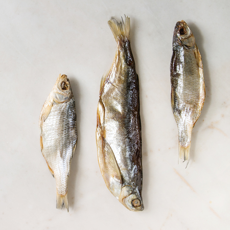 Dried fish or stockfish over white marble background. Flat lay, space. Square image