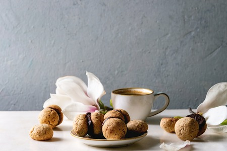 Baci di dama homemade italian hazelnut biscuits cookies with chocolate cream served in ceramic plate with cup of espresso coffee and magnolia flowers over white marble table. Copy space Stok Fotoğraf - 122998619
