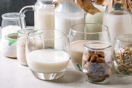 Varietà di noci vegane senza lattosio e latte di grano mandorla, nocciola, cocco, riso, avena in bottiglie di vetro con ingredienti sopra su tavolo bianco con sfondo blu.