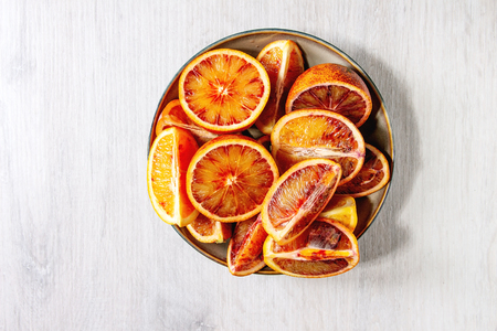 Group of fresh organic Sicilian blood oranges sliced and whole in ceramic plate over white wooden background. Flat lay, space