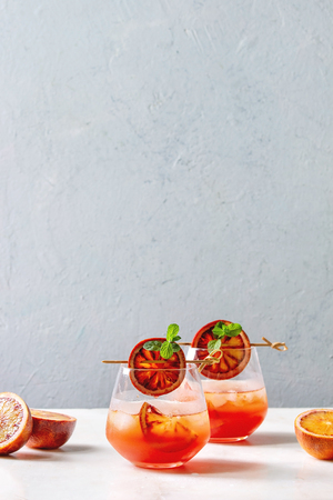 Blood orange iced cocktails in glasses, decorated by slice of oranges and fresh mint on skewers, served on white marble table with grey wall at background. 写真素材