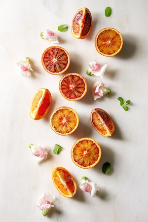 Group of fresh organic Sicilian blood oranges sliced and whole, edible flowers, mint leaves over white marble background. Flat lay, space Stock Photo