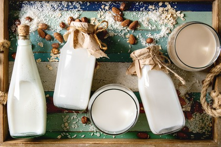 Variety of non-dairy vegan lactose free nuts and grain milk almond, hazelnut, coconut, rice, oat in glass bottles with ingredients above in wooden colorful plank tray. Flat lay, space