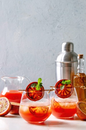 Blood orange iced cocktails in glasses, decorated by slice of oranges and fresh mint on skewers, served with shaker, jug of juice, bottle of rum on white marble table with grey wall at background. Фото со стока
