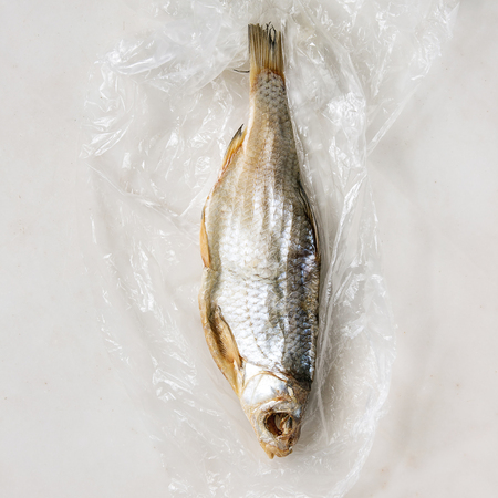Dried fish or stockfish on plastic bag over white marble background. Flat lay, space. Square image Stockfoto