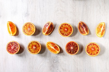 Group of fresh organic Sicilian blood oranges sliced and whole in row over white wooden background. Flat lay, space Stock Photo